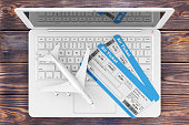 Online Booking Concept. Airline Boarding Pass Tickets with Jet Airplane over Laptop on a Wooden Table extreme closeup. 3d Rendering
