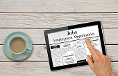 Online job hunting Hand with computer tablet reading employment ads on table with coffee - recruitment concept
