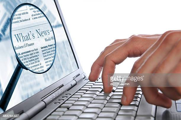 OnLine News, man's hands laptop keyboard, magnifying glass on screen