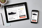 Online shop concept on tablet and smartphone screen over gray table. All screen content is designed by me. Flat lay