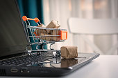 Online shopping concept. Shopping cart, small boxes, laptop on the desk