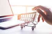Online shopping concept with woman hand and cart