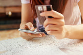 Woman is making online shopping with mobile phone. She use credit card and the smartphone.