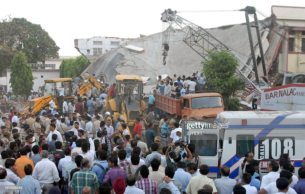 Onlookers and rescue personnel are pictured at the scene of a hospital collapse in Bhopal on April 26, 2013. Up to 15 people, mostly patients, were feared trapped after part of a hospital roof caved in on Friday in the central Indian city of Bhopal, officials and eyewitnesses said.