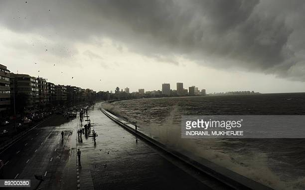 Onlookers and revellers throng the Marine Drive promenade on the Arabian Sea front as high tides lash its shores in Mumbai on July 23 2009 The civic...
