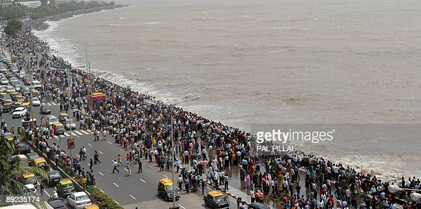 Onlookers and revellers throng the Marine Drive promenade on the Arabian Sea front as high tides lash its shores in Mumbai on July 24 2009 The peak...
