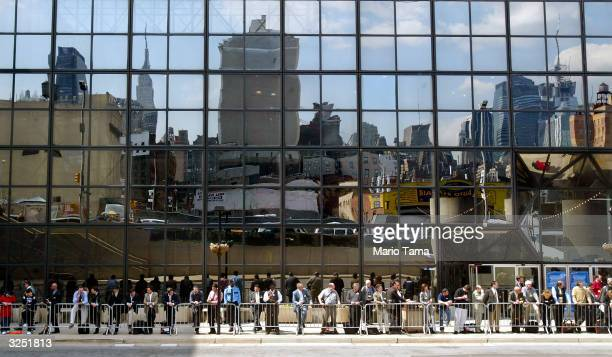Onlookers await an automobile demonstration as the Manhattan skyline is reflected behind them in the Jacob Javits Convention Center windows during a...