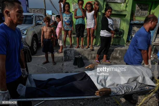 Onlookers cover their noses as funeral workers carry a body of a shooting victim unclaimed for months to be buried in a mass grave in Navotas north...