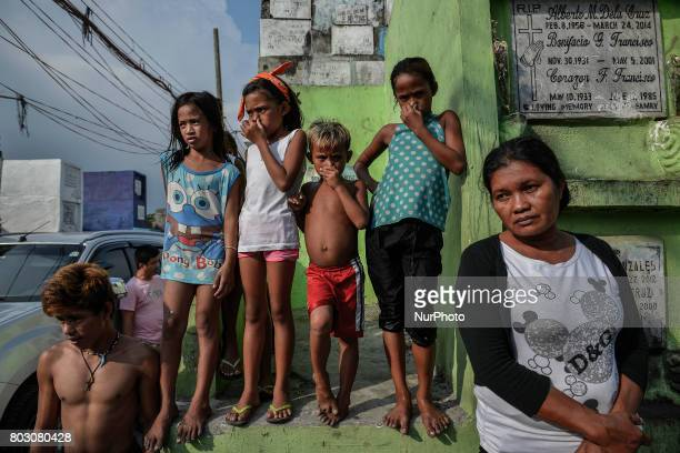 Onlookers cover their noses as funeral workers carry bodies of shooting victims unclaimed for months to be buried in a mass grave in Navotas north of...