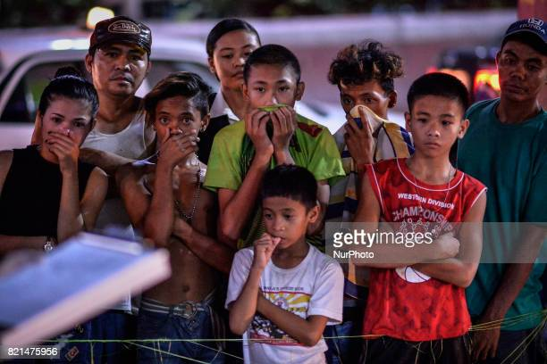 Onlookers cover their noses near the scene where a man was killed by unknown assailants in Manila Philippines July 17 2017 The United States congress...