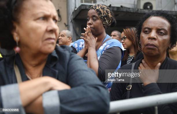 Onlookers gather as Catholics march in a procession while celebrating the holiday of Corpus Christi on June 15 2017 in Sao Goncalo Brazil The...