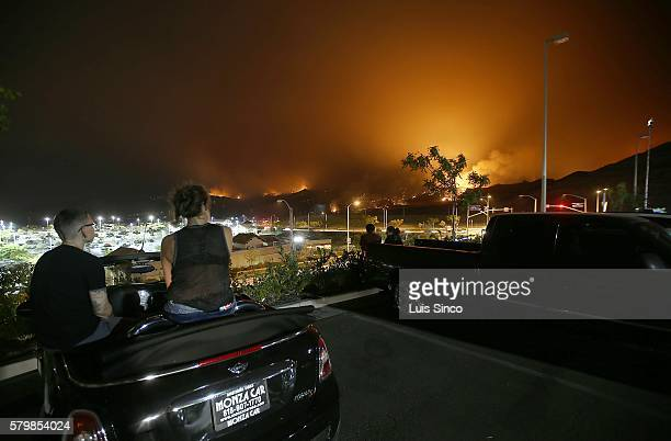 Onlookers gather at the parking lot of a shopping mall along Golden Valley Road in Santa Clarita to watch the Sand fire burn in the hills above the...