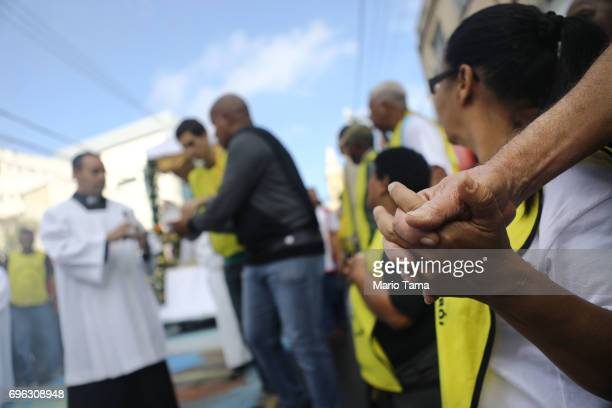 Onlookers hold hands as Catholics march in a procession while celebrating the holiday of Corpus Christi on June 15 2017 in Sao Goncalo Brazil The...