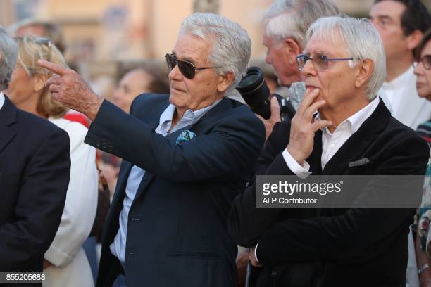 Onlookers including French actress Brigitte Bardot's fourth and current husband Bernard d'Ormale and Italian artist Milo Manara gather beside a...