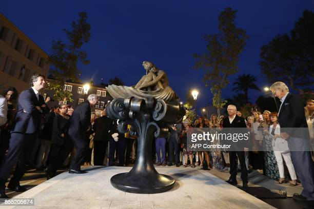 Onlookers including Italian artist Milo Manara and Bardot's fourth and current husband Bernard d'Ormale gather beside a statue of French actress...
