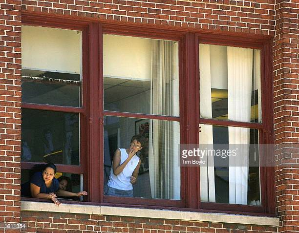 Onlookers peer out their window as they watch police activities on the street in front of an adjacent apartment building August 28 2001 south of...