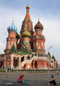 Onlookers pose for photos outsdie St Basil's Cathedral ahead of the 14th IAAF World Championships at on August 6 2013 in Moscow Russia