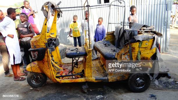 Onlookers stand beside a blood stained taxi rickshaw at the scene of three suicide bomb blasts that left 13 people dead in Maiduguri northeast...