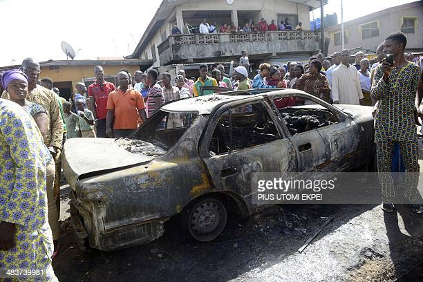 Onlookers stand beside a car that got burnt with the occupants following a spark from a power cable that fell from a pole supplying electricity to a...