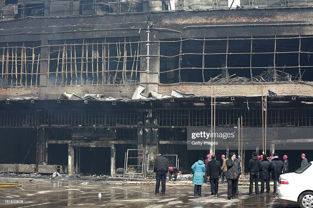 Onlookers stand by the site of a fire at a supermarket on February 17, 2013 in Changzhi, China. The supermarket caught fire at 4:10 a.m. today and was put out two hours later without any reports of casualties.