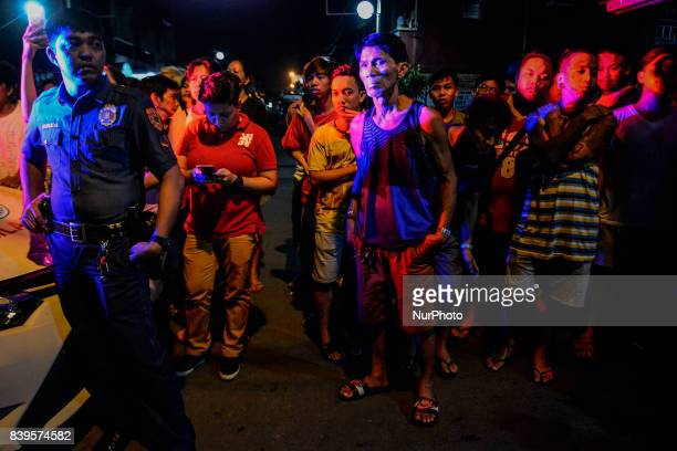 Onlookers stand near the scene where a man was killed by police following a police operation in Manila Philippines August 17 2017 Amidst the drug...