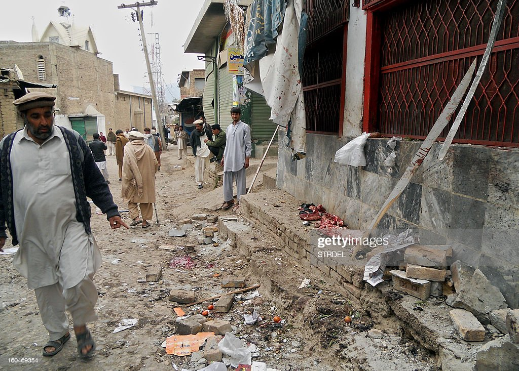 Onlookers stand over the site of a bomb blast outside a Shiite Muslim mosque in Hangu on February 1, 2013. A suicide bomber targeted a Shiite Muslim mosque in northwest Pakistan on Friday, killing 21 people and wounding up to 50 as worshippers poured out of weekly prayers, officials said.