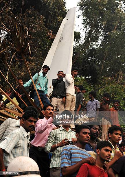 Onlookers take photographs as rescue personnel and volunteers work at the crash site of an Air India Boeing 737800 aircraft which crashed upon...