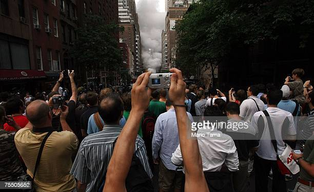 Onlookers take photos at the scene of a steam pipe explosion on Lexington Avenue July 18 2007 in New York City Steam and mud were forced from the...