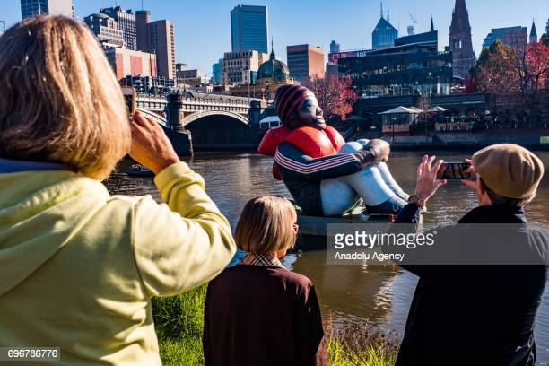 Onlookers take photos of the travelling artwork titled 'Inflatable Refugee' on the Yarra River on June 17 2017 in Melbourne Australia The five...