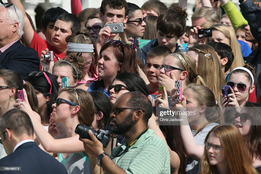 Onlookers take pictures with their smartphones as they wait for HRH Prince Harry to arrive during the second day of his visit to the United States at Arlington National Cemetery on May 10, 2013 in Arlington, Virginia. HRH will be undertaking engagements on behalf of charities with which the Prince is closely associated on behalf also of HM Government, with a central theme of supporting injured service personnel from the UK and US forces.