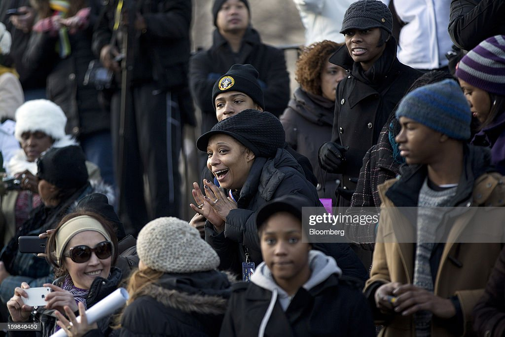Onlookers wait for U.S. President Barack Obama along the parade route during the inauguration in Washington, D.C., U.S., on Monday, Jan. 21, 2013. A crowd estimated by police to be as large as 700,000, including warmly dressed women with American flags stuck in their hair, a smattering of celebrities and many Republicans, gathered today to witness Obama take his second oath of office on the steps of the U.S. Capitol. Photographer: Andrew Harrer/Bloomberg via Getty Images