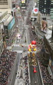 Onlookers watch as giant balloons float down Broadway in Times Square during the 78th Annual Macy's Thanksgiving Day Parade November 25 2004 in New...