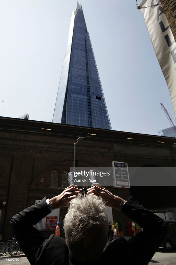 Onlookers watch as members of Greenpeace scale the Shard, the tallest building in western Europe, on July 11, 2013, in London, England. The six female protesters began their unauthorised ascent of the 310 metre high skyscraper shortly after 4am with the intention of highlighting the environmental damage caused by drilling for oil in the Arctic by Shell.