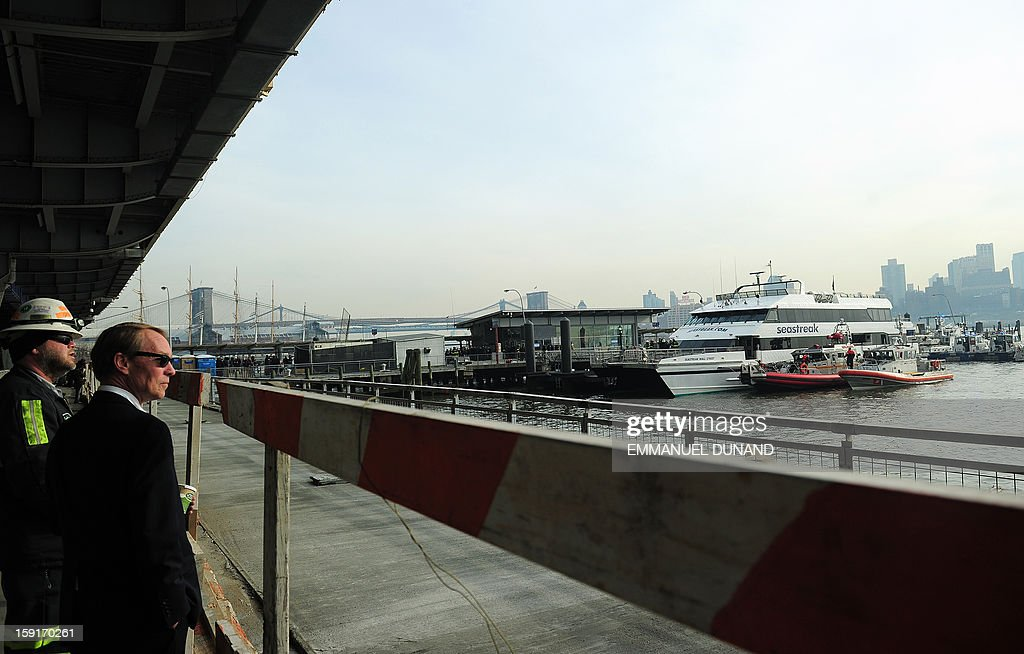 Onlookers watch as security personel inspect the commuter ferry that slammed into a pier in New York, January 9, 2013. About 50 people were injured when a rush-hour ferry packed with commuters smashed into a pier in New York City on Wednesday, firefighters said. The accident took place at 8:45 am (1345 GMT) on Pier 11 in the East River in lower Manhattan, not far from Wall Street, the New York Fire Department said. The ferry was arriving from New Jersey. 'We are assessing 50 patients on the scene right now. We don't know what kind of injuries they have,' an NYFD spokeswoman said. AFP PHOTO/EMMANUEL DUNAND