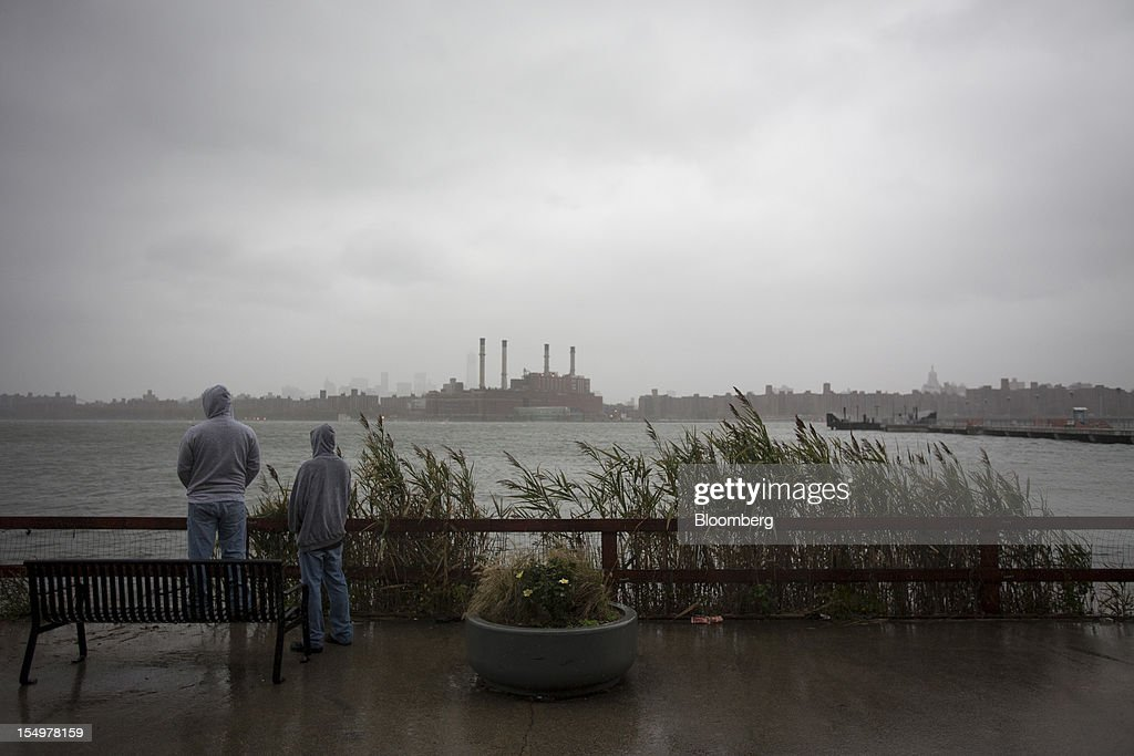 Onlookers watch as the storm gathers over Manhattan in New York, U.S., on Monday, Oct. 29, 2012. Hurricane Sandy strengthened on its path toward New Jersey, where it is predicted to make landfall today while bringing a life-threatening storm surge as it whips a region of 60 million people with high winds and rain. Photographer: Scott Eells/Bloomberg via Getty Images