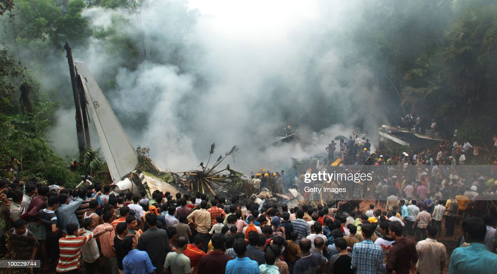 Onlookers watch firemen and paramilitary personnel conduct rescue work at the airline crash site, on May 22, 2010 in Mangalore. An Air India Express Boeing 737-800 series aircraft overshot the runway on arrival and crashed into a forest. Airline officials say 8 people have been rescued while nearly 160 others are feared dead.