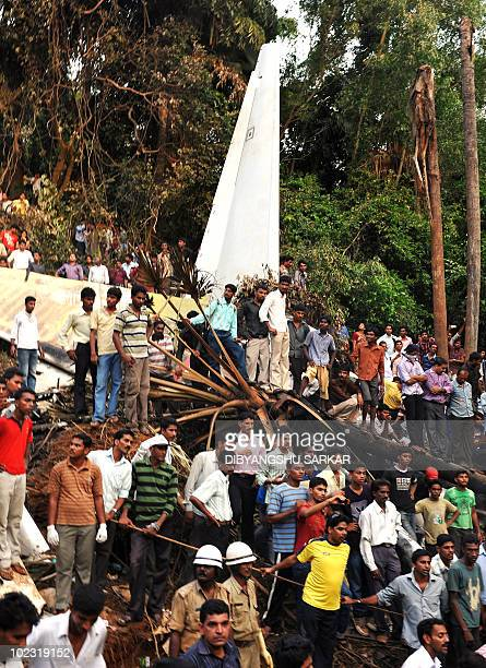 Onlookers watch on as rescue personnel and volunteers work at the crash site of an Air India Boeing 737800 aircraft which crashed upon landing in...