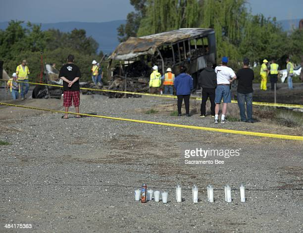 Onlookers watch on Friday April 11 2014 as Caltrans workers begin clearing the charred remains of a charter bus that collided with a FedEx tractor...