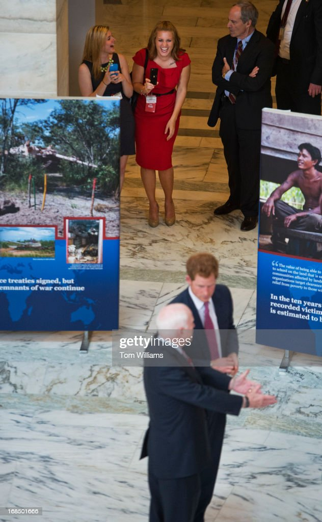 Onlookers watch Prince Harry of Wales and Sen. John McCain, R-Ariz., tour an anti-landmine photo exhibit sponsored by the HALO Trust Russell rotunda. This is the first stop on Prince Harry's seven day trip around the U.S.