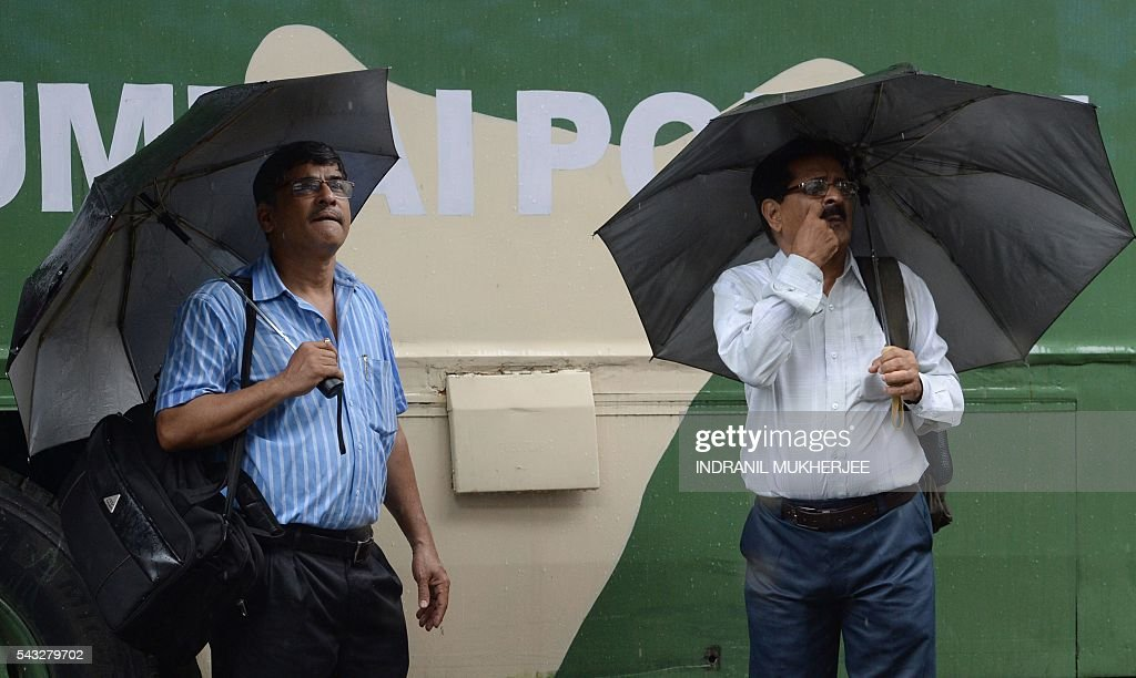 Onlookers watch share prices on a digital broadcast on the facade of the Bombay Stock Exchange (BSE) during a downpour in Mumbai on June 27, 2016. Britain battled to stop worldwide Brexit alarm on June 27 as sterling crumbled to a three-decade low against the dollar, while bank, airline and property shares plummeted. Other world markets steadied a little after Britain's June 23 vote to abandon the European Union wiped $2.1 trillion off international equity values Friday. MUKHERJEE