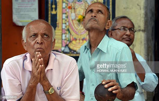 Onlookers watch share prices on a screen outside the Bombay Stock Exchange in Mumbai on August 24 2015 The plummenting Chinese market on August 24...