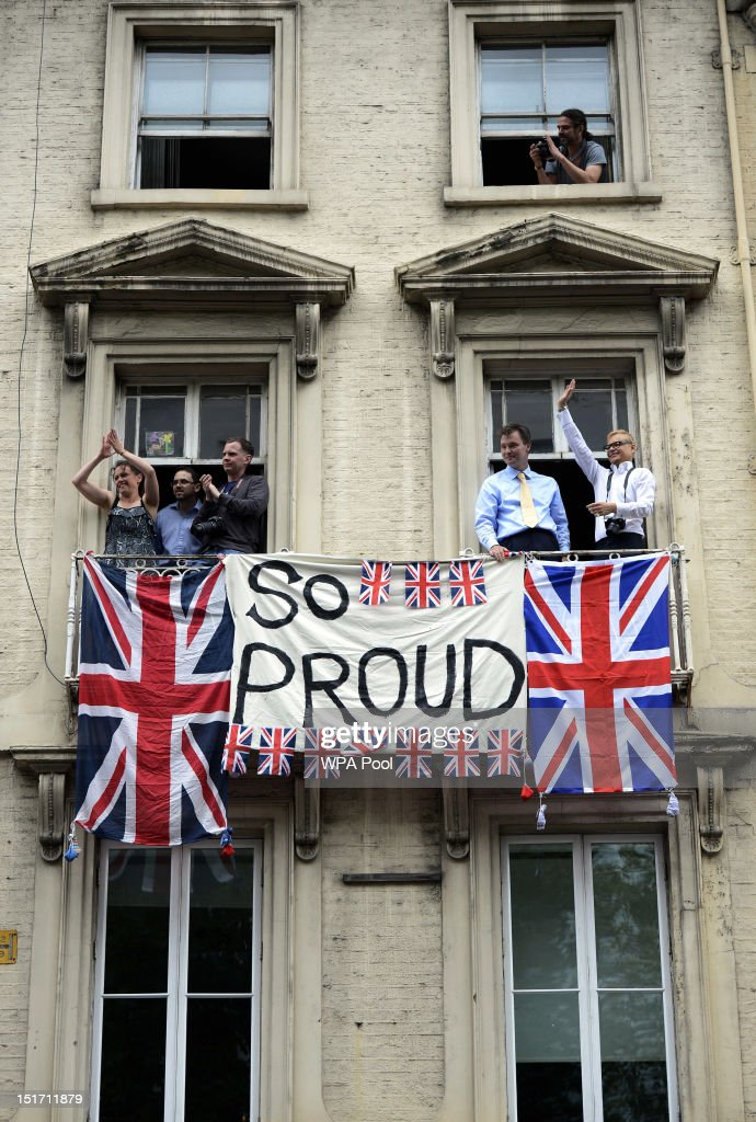 Onlookers wave from windows during the London 2012 Victory Parade for Team GB and Paralympics GB athletes on September 10 2012 in London England