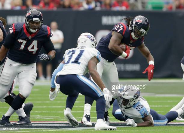 Onta Foreman of the Houston Texans is tackled by Jayon Brown of the Tennessee Titans and Kevin Byard at NRG Stadium on October 1 2017 in Houston Texas