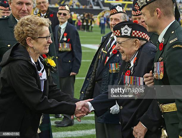 Ontario premier Kathleen Wynne skates hands with a veteran prior to play between the Montreal Alouettes and the Hamilton TigerCats in a CFL football...