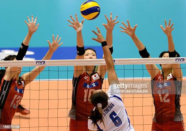 Onuma Sittirak of Thailand spikes the ball in front of Japanese blocks Risa Shinnabe Nana Iwasaka and Yuki Ishii during their FIVB volleyball women's...