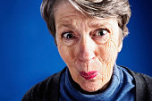 A wrinkled old woman screws up her face, wincing in pain, embarrassment, or shock at something.