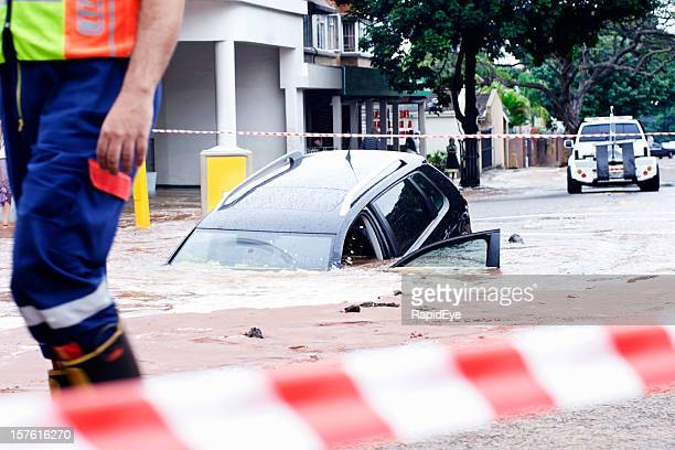 Oops! Car slipping into pothole in flooded street