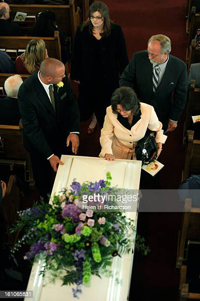 Opal Dick the mother of Linnea Dick touches the casket of her daughter as it is wheeled out of St Andrew's Episcopal Church after the funeral...
