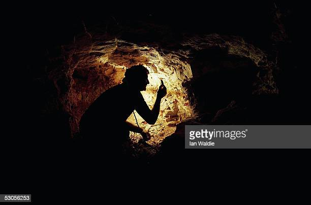 Opal miner John Shane inspects extracted rock in his underground mine June 12 2005 in the outback mining town of Coober Pedy Australia Australia...