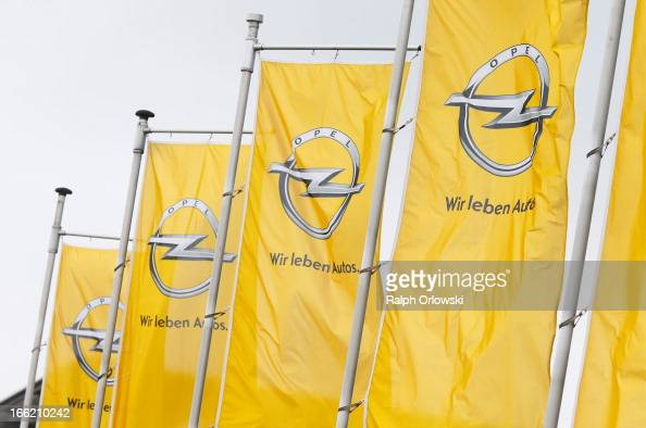 Opel flags flatter in the wind at the headquarters of German carmaker before a press conference on April 10 2013 in Ruesselsheim Germany German...